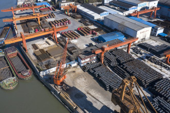 Barges sit docked at a steel stockyard in this aerial photograph in Shanghai on Monday.