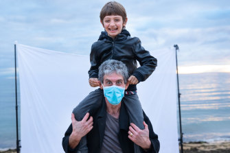 Associate Professor Daryl Efron flashes a big smile through his mask with seven-year-old son Luca.
