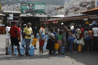 People wait in line to stockpile drinking water in Port-au-Prince ahead of further protests.