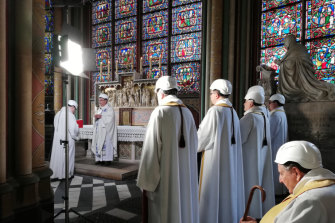 The Archbishop of Paris Michel Aupetit, second left, leads the first mass in a side chapel, two months after a devastating fire engulfed the Notre-Dame de Paris cathedral.