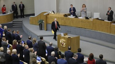 Russian President Vladimir Putin, centre, arrives to applause from the members of the State Duma.