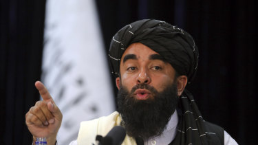 In front of a Taliban flag, Taliban spokesman Zabihullah Mujahid speaks at at his first news conference, in Kabul, on Tuesday. The group's websites were offline on Saturday.