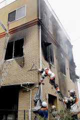 Firefighters work on the scene of the fire at the Kyoto Animation studio on Thursday.
