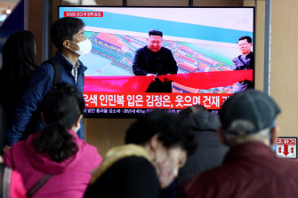 People watch a television broadcast reporting the appearance of North Korean leader Kim Jong-un in Seoul.