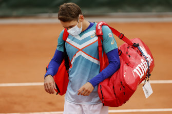 Short and sharp: Alex de Minaur leaves the court after losing to Marco Cecchinato in the first round.