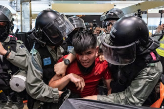 Riot police detain a man during protests at a shopping mall on Saturday.