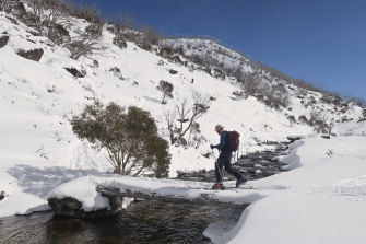 Crossing the Guthega River, skiing and snowboarding in the Australian alpine backcountry, the Snowy Mountains main range.