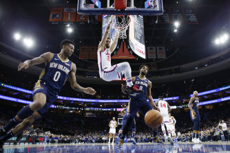 Ben Simmons hangs from the rim after a dunk past New Orleans Pelicans' Nickeil Alexander-Walker and Jahlil Okafor.