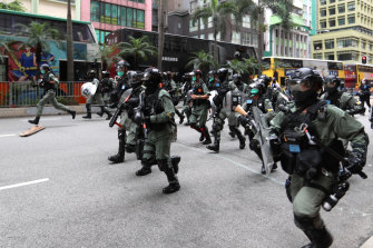 Riot police charge at demonstrators.
