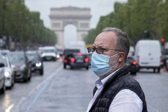 A man crosses the Champs Elysees avenue in Paris on Monday.