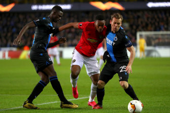 United's Anthony Martial is challenged by Club Brugge's Odilon Kossounou and Ruud Vormer.