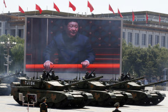 Chinese President Xi Jinping is displayed on a screen as Chinese battle tanks take part in a parade commemorating the 70th anniversary of Japan's surrender during World War II held in front of Tiananmen Gate in Beijing.