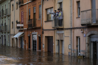 People stand on a balcony following a storm in Girona, Spain. At least 11 have died and five people remain missing.