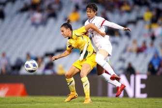 Chloe Logarzo of the Matildas and Li-Ping Zhuo of Taiwan compete for the ball at Campbelltown.