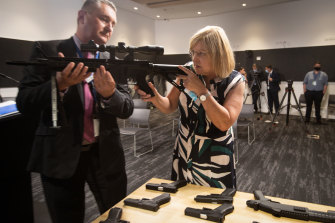 Detective Inspector Mick Daly shows Police Minister Lisa Neville an illegal guns seized by police during the launch of the illicit firearms unit in Melbourne.