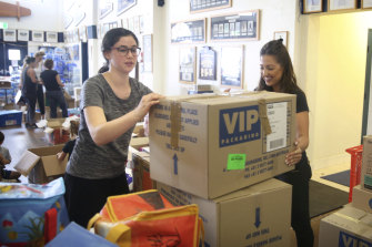 Volunteers and Bondi SLSC members Leila Freedman and Victoria Nessis prepare donations for delivery.