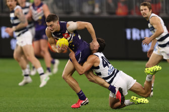 Darcy Tucker tries to break the Luke Dahlhaus tackle.