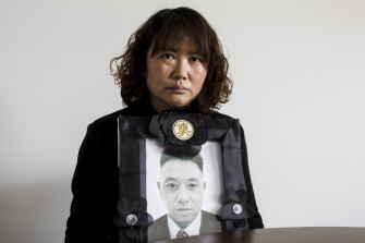 Lihong Wei holds a portrait of her husband, Xiaojun Chen, who was killed while working for a delivery company in Sydney.