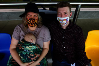 Sarah McKenzie and Matthew Bourke with their baby Finley Bourke in the grandstand.