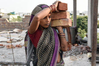 A woman carries bricks at a construction site on a hot summer evening in New Delhi.