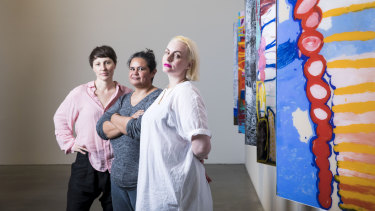 Artists Izabela Pluta, Janet Fieldhouse and Melanie Jame Wolf next to artworks by Daisy Japulija, Sonia Kurarra, Tjigila Nada Rawlins and Ms Uhl of the Mangkaja Arts Resource Agency at the Museum of Contemporary Art.
