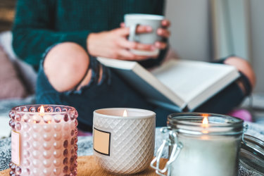 Cropped shot of an unrecognizable young woman relaxing with a book and a cup of coffee on her bed at home A woman relaxing on her bed reading with candles. Photo: iStock