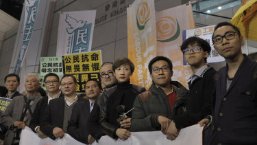 Tanya Chan stands with other current and former lawmakers for a picture before walking toward a police station in Hong Kong.