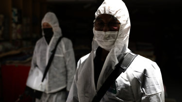 Disinfection professionals, wearing protective gear, spray antiseptic solution to guard against the coronavirus at a department store in Seoul, South Korea.