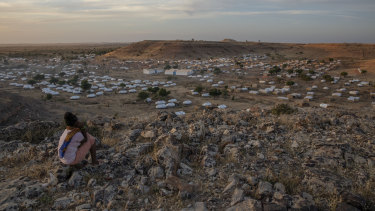 A Tigray girl sits atop a hill overlooking the Umm Rakouba refugee camp, hosting people who fled the conflict in the Tigray region of Ethiopia, in Qadarif, eastern Sudan.