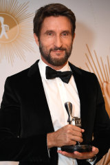 Jonathan LaPaglia, host of Australian Survivor, poses with the Logie for most popular reality program.