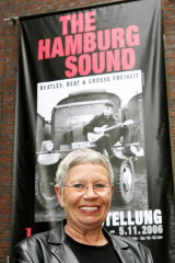 Astrid Kirchherr poses in front of a poster of the exhibition 'The Hamburg Sound' in the Hamburg Museum, in Hamburg, in 2006.