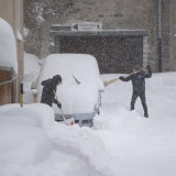 Children remove snow from a car in the the village of Andermatt, Switzerland on Sunday.