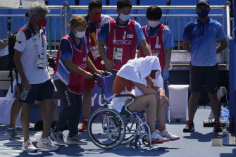 Spain's Paula Badosa is helped off the court in a wheelchair in Tokyo.