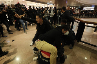 Plainclothes police officers arrest protesters in a mall on Christmas Eve in Hong Kong.