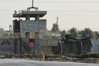 A Turkish military armoured vehicle fires towards the Syrian town of Tal Abyad from the Turkish side of the border.