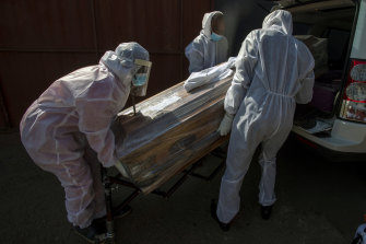 Funeral home workers in protective suits carry the coffin of a woman who died from COVID-19 into a hearse in Katlehong, near Johannesburg.