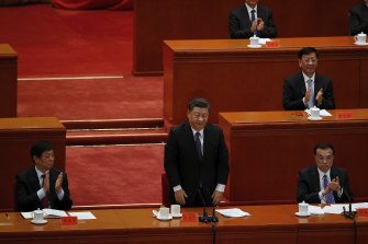Party officials applaud as Chinese President Xi Jinping, standing, delivers his speech on the 70th anniversary of the Chinese army entering North Korea to resist the US army.