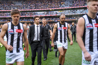 A dejected Steele Sidebottom (second from right) leaves the field with his Pies teammates.