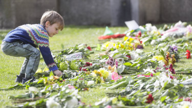 A child lays flowers outside Windsor Castle, where Prince Philip died.
