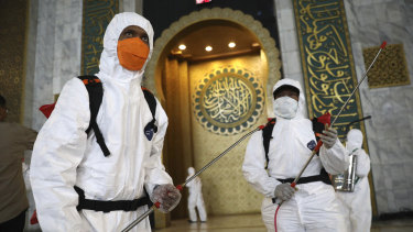 Workers prepare to disinfect al-Akbar mosque in Surabaya, East Java, Indonesia