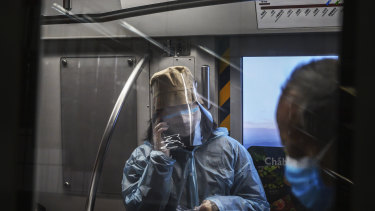 A woman wears a protective mask and face shield as she rides the subway in Beijing.
