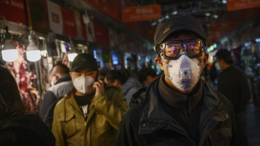 A Chinese shopper wears a mask at a Beijing market.