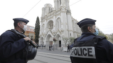 Police officers stand guard near Notre Dame church in Nice after an attacker beheaded a woman and killed two others.