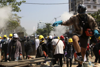 Protesters are dispersed as riot police fired tear gas behind a makeshift barricade in Yangon.