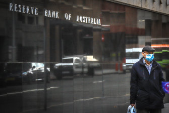 A pedestrian wearing a face mask walks past the Reserve Bank of Australia.