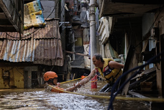 A rescue worker helps his colleague as they navigate a flooded Jakarta neighbourhood on January 2.