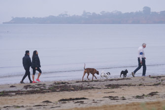 Walkers at Mentone Beach in Melbourne.