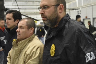 "US Drug Enforcement Administration, authorities escort Joaquin ""El Chapo"" Guzman, centre, from a plane to a waiting caravan of SUVs at Long Island MacArthur Airport in New York in 2017."
