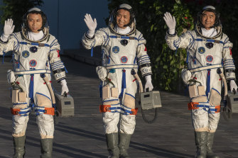 From Left, Chinese astronauts Tang Hongbo, Nie Haisheng and Liu Boming wave before launch of the Senzhou-12 n Jiuquan, Gansu province, on June 17.