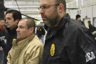 """US Drug Enforcement Administration, authorities escort Joaquin """"El Chapo"""" Guzman, centre, from a plane to a waiting caravan of SUVs at Long Island MacArthur Airport in New York in 2017."""